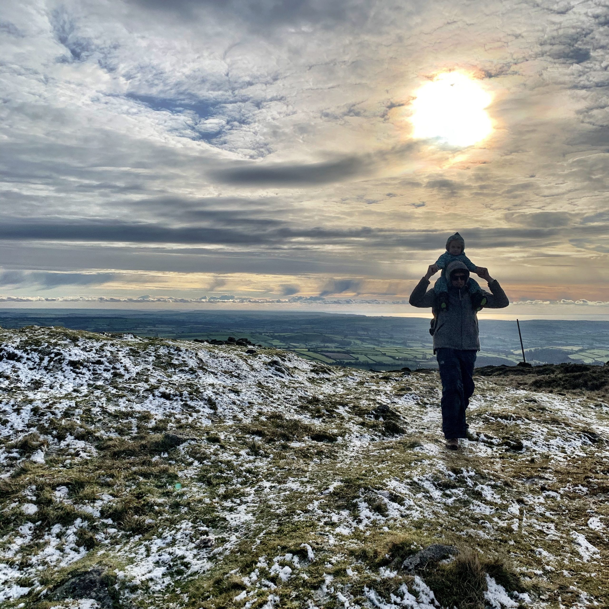 A father walks on snowy Dartmoor with his son on his shoulders