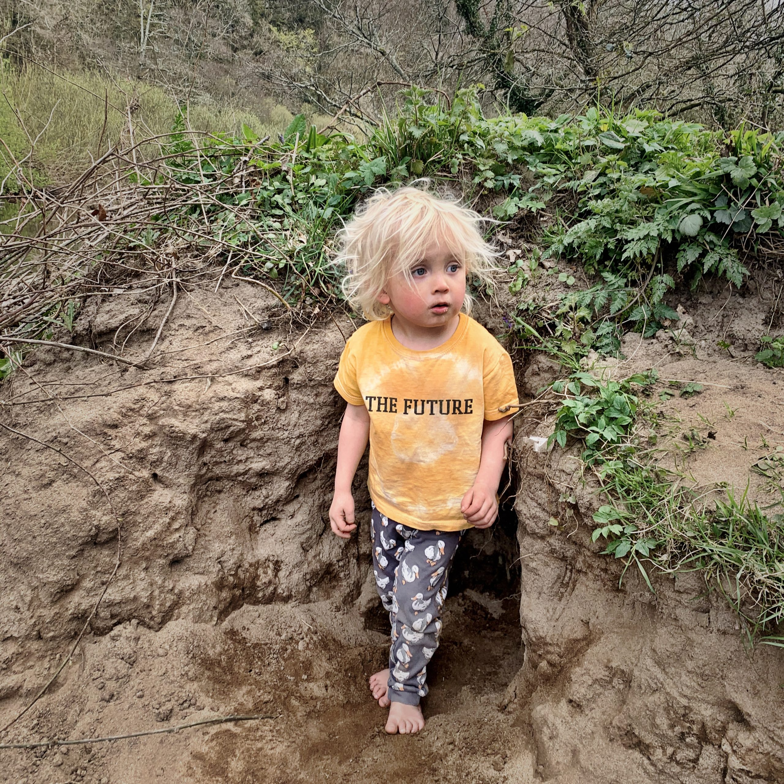 A barefoot child wearing a t-shirt with the words 'the future'